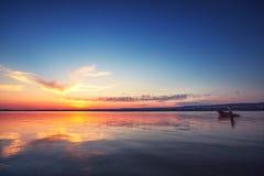 Coucher du soleil au-dessus du lac et de la silhouette des pêcheurs Photo libre de droits