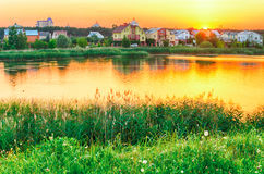 Coucher du soleil au-dessus du lac et des maisons Image libre de droits