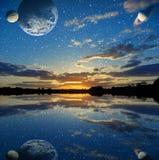 Coucher du soleil au-dessus du lac sur un fond de ciel avec des planètes Photo stock