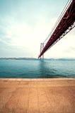 Coucher du soleil au-dessus du pont de 25 de Abril au-dessus du Tage et du Christ m Images stock