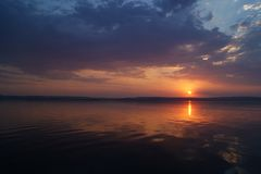 Coucher du soleil au-dessus du fleuve Le soleil dans les nuages se repose à travers la rivière Photo stock
