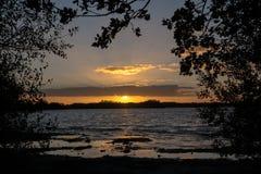 Coucher du soleil au-dessus du lac, vue par les silhouettes noires d'arbre dessus images libres de droits