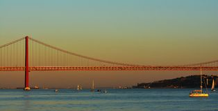 Coucher du soleil au-dessus du Tage avec 25 De Abril Bridge à Lisbonne Images libres de droits