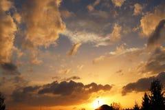Coucher du soleil au-dessus du village Coloration dramatique du ciel égalisant avec des cumulus Gamme d'or de couleurs de nature  image stock