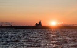 Coucher du soleil au phare de roche d'exécution image stock