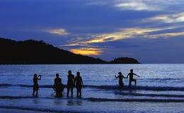 coucher du soleil avec des gens en plage   images stock