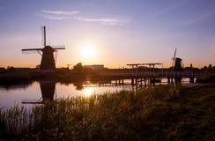Coucher du soleil avec des moulins à vent néerlandais traditionnels et un pont en bois en K Photos libres de droits