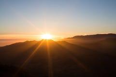 Coucher du soleil avec des rayons derrière la colline Photographie stock
