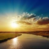 Coucher du soleil avec des rayons en nuages au-dessus de rivière Photo libre de droits