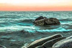 Coucher du soleil avec des roches dans un océan vert photos stock