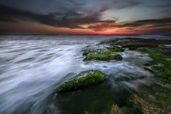 Coucher du soleil avec des roches sur le bord de la mer image stock