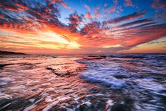 Coucher du soleil avec des roches sur le bord de la mer photo stock