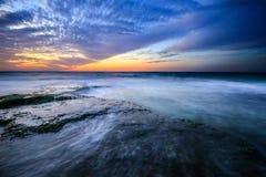 Coucher du soleil avec des roches sur le bord de la mer photos stock