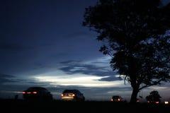 Coucher du soleil avec des voitures Photographie stock