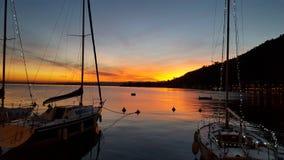 Coucher du soleil avec la montagne, le lac et les bateaux à voile Image libre de droits