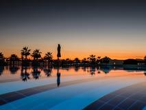Coucher du soleil avec la paume de silhuettes et réflexion dans la piscine photo libre de droits