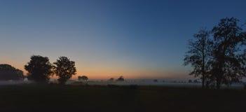 Coucher du soleil avec le brouillard photographie stock
