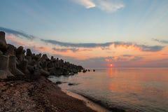 Coucher du soleil avec le soleil et des rayons de soleil en mer Photographie stock