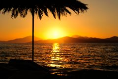Coucher du soleil avec les montagnes, la mer et la paume Images libres de droits