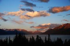 Coucher du soleil avec les montagnes, le lac, et les arbres silhouettés Photographie stock libre de droits