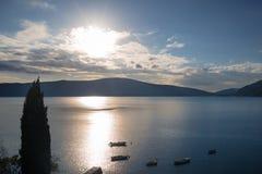 Coucher du soleil avec les nuages dramatiques sur le fond d'une baie et des montagnes Photos stock