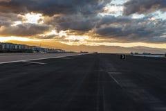 Coucher du soleil avec les nuages orageux au-dessus de la piste d'aéroport au Gibraltar Photos stock