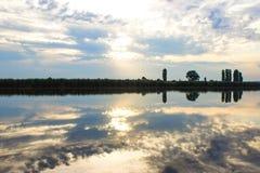 Coucher du soleil avec les nuages, rayons légers au-dessus de rivière avec des réflexions Photographie stock libre de droits