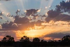 Coucher du soleil avec les rayons légers et les nuages Images libres de droits