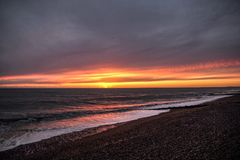 Coucher du soleil avec un ciel nuageux sur la plage photo libre de droits