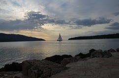 Coucher du soleil avec un voilier Image libre de droits