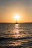 Coucher du soleil avec une navigation silhouettée de bateau Photos stock