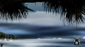 Coucher du soleil bleu à travers des yachts sur l'eau Photo libre de droits