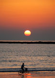 Coucher du soleil brumeux avec le cycliste Photographie stock