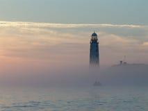 Coucher du soleil brumeux, petit bateau et phare Image libre de droits