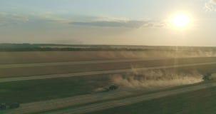Coucher du soleil Champ et tracteurs de blé recueillant dans les cultures banque de vidéos