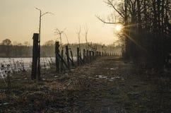 Coucher du soleil chaud au-dessus d'assèche et de route en hiver Photographie stock libre de droits