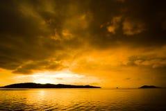 Coucher du soleil coloré au-dessus de l'eau ondulée Photos stock
