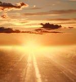 Coucher du soleil coloré au-dessus de route de campagne sur le ciel dramatique Image libre de droits