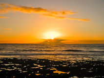 Coucher du soleil coloré avec des nuages par l'océan Photographie stock