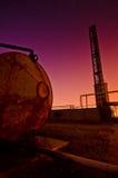 Coucher du soleil coloré derrière une grue et un réservoir industriels Image libre de droits