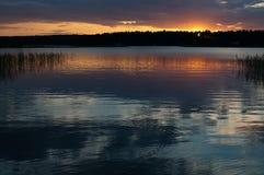Coucher du soleil coloré paisible par un lac avec des réflexions de ciel photo libre de droits