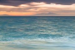 Coucher du soleil cramoisi sur le rivage du witt de ciel orange et de mer calme Photographie stock libre de droits