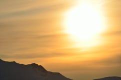 Coucher du soleil d'or énorme au-dessus de crête de montagne neigeuse Photos stock