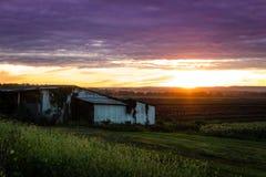 Coucher du soleil d'été au-dessus de ferme et de cabane humbles pendant la récolte maximale Photo libre de droits