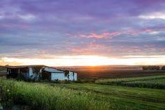 Coucher du soleil d'été au-dessus de vallée et de cabane de ferme pendant la récolte maximale Photographie stock libre de droits
