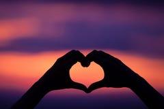 Coucher du soleil d'amour de forme de coeur de main Images stock