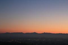 Coucher du soleil d'or au-dessus de la colline avec l'horizon de montagnes Photos stock