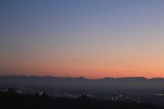 Coucher du soleil d'or au-dessus de la colline avec l'horizon de montagnes Image stock