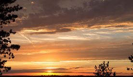 Coucher du soleil d'or avec des filets des nuages Photographie stock