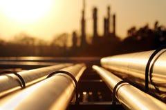 Coucher du soleil d'or dans la raffinerie de pétrole brut avec le réseau de pipe-lines photographie stock